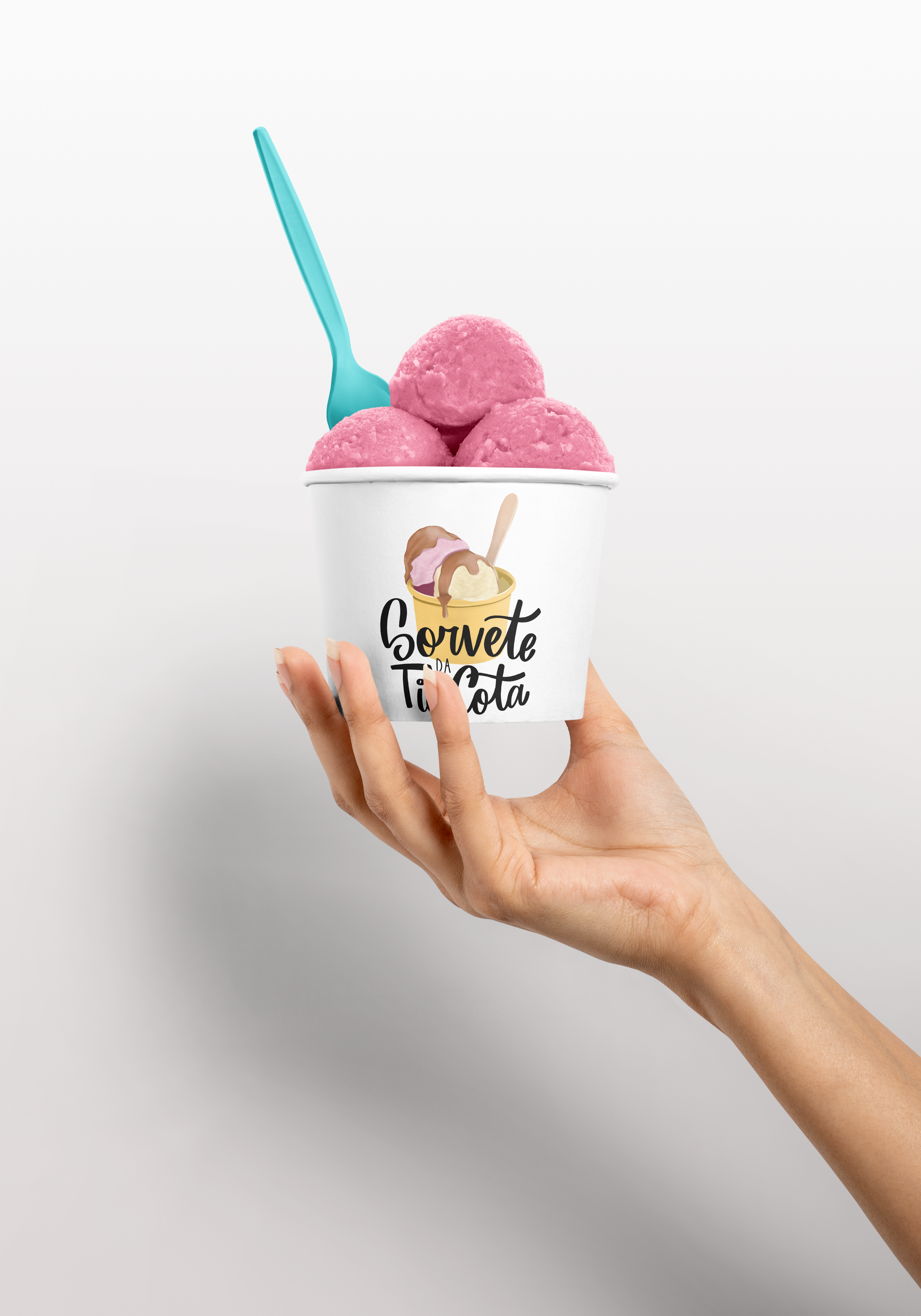 woman holding ice cream cup with 3 scoops of pink ice cream and a blue spoon